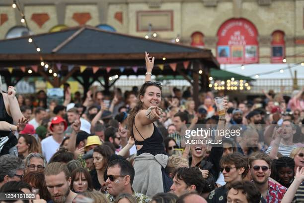 Festival-goers dance at the Kaleidoscope Festival in Alexandra Palace Park in London on July 24, 2021. - The one-day Kaleidoscope festival is set to...