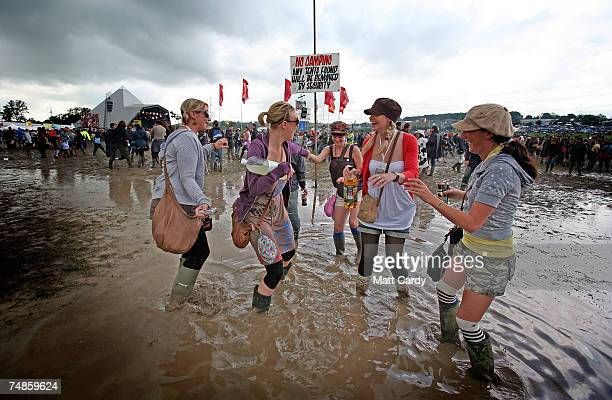 Festivalgoers dance in a puddle by the Pyramid Stage at Worthy Farm Pilton near Glastonbury on June 22 2007 in Somerset England The festival that was...