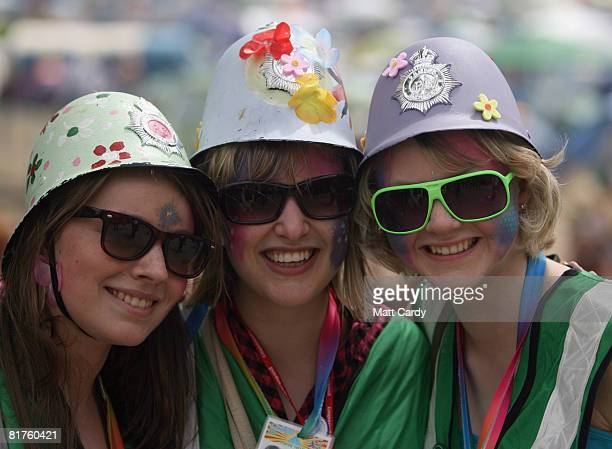 Festivalgoers dressed as 'green' police smile as they pose for photographs at the Glastonbury Festival at Worthy Farm Pilton on June 29 2008 in...