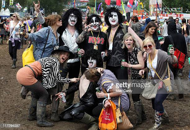 Festivalgoers dressed as the band Kiss meet some groupies at the Glastonbury Festival site at Worthy Farm Pilton on June 25 2011 This year's festival...