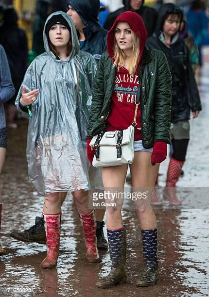 Festivalgoers enjoy the atmosphere as rain falls during day 1 of the 2013 Glastonbury Festival at Worthy Farm on June 27 2013 in Glastonbury England