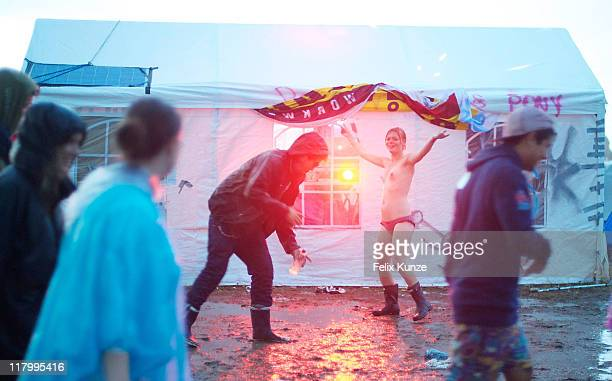 Festivalgoers enjoy the atmosphere during heavy rainfall on day three of Roskilde Festival 2011 on July 2 2011 in Roskilde Denmark