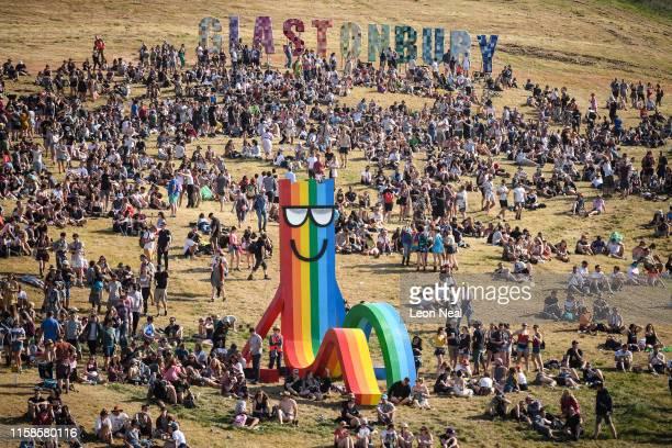 Festivalgoers enjoy the evening light during day one of Glastonbury Festival at Worthy Farm Pilton on June 26 2019 in Glastonbury England Glastonbury...