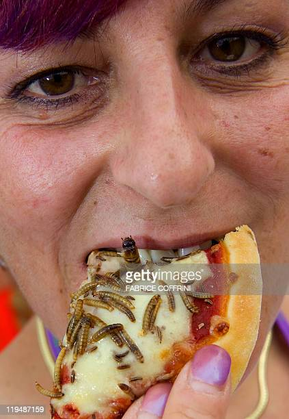 A festivalgoers enjoys an 'insects pizza' at one of the many food stalls during the 34th edition of the Paleo festival on July 22 2009 in Nyon The...