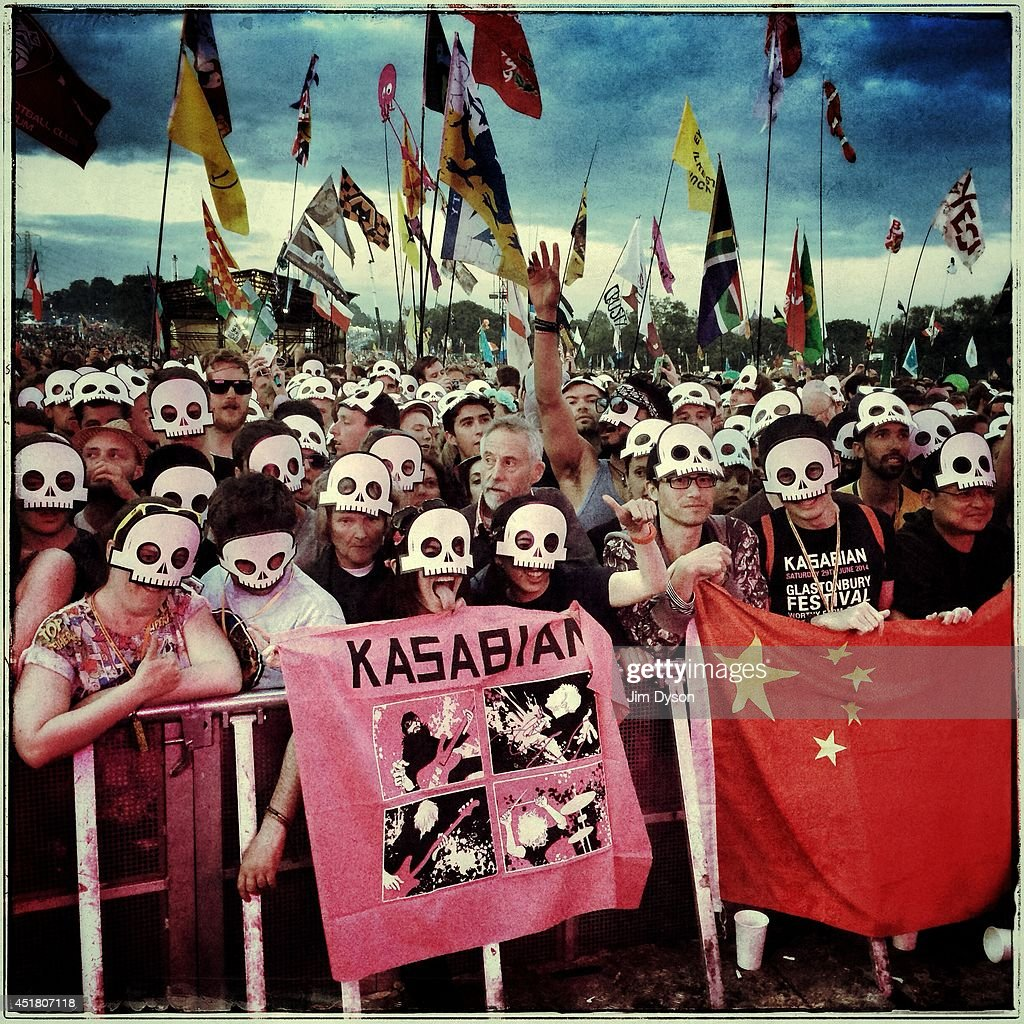 Festival-goers in masks wait for Kasabian to take to the stage during the Glastonbury Festival at Worthy Farm in Pilton on June 29, 2014 in Glastonbury, England.