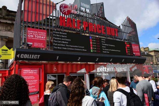 Festivalgoers on The Mound precinct queue outside the 'Half Price Hut' ticket office during the Edinburgh Festival Fringe on August 16 2018 in...