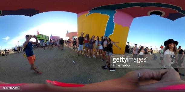 Festivalgoers pose for a photo by the art installation titled 'Is this what brings things into focus' during day 3 of the Coachella Valley Music And...