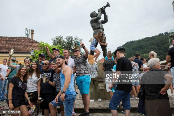Festivalgoers pose for pictures in front of the trumpeter statue in the city centre during the trumpet and brass band festival in the Serbian village...