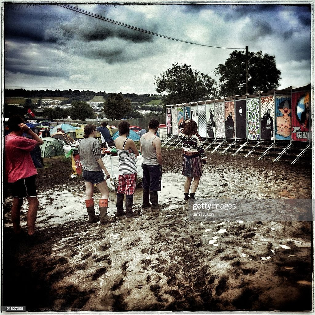 Festival-goers queue for the toilets in the mud during the Glastonbury Festival at Worthy Farm in Pilton on June 29, 2014 in Glastonbury, England.