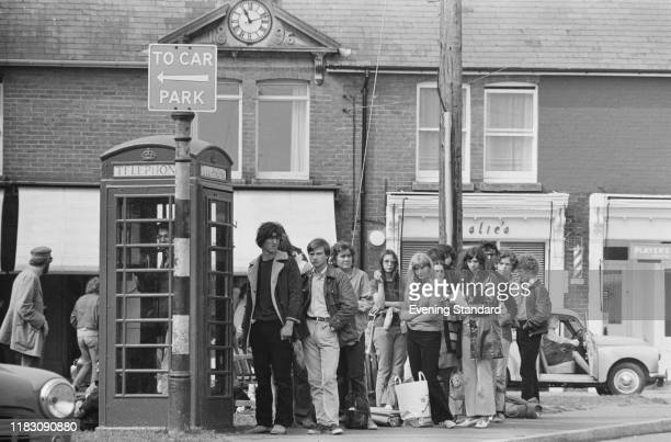 Festivalgoers queuing up to make phone calls outside a red telephone box on the Isle of Wight while attending the Isle of Wight Festival UK 26th31st...