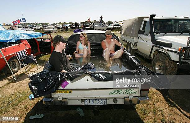 Festivalgoers relax in a homemade pool in the back of their ute as revellers gather to celebrate Australia's affinity for the iconic ute or pickup at...