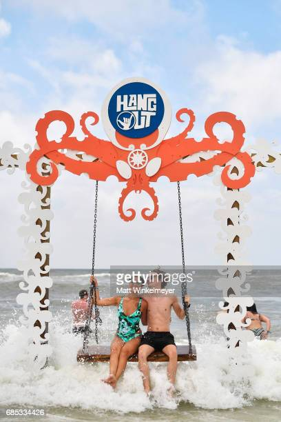 Festivalgoers sit on a swing in the ocean at the Beach Club during 2017 Hangout Music Festival on May 19 2017 in Gulf Shores Alabama