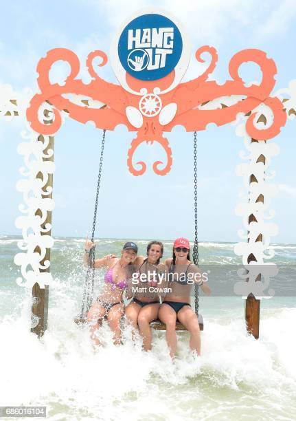 Festivalgoers sit on a swing in the ocean at the Beach Club during the 2017 Hangout Music Festival on May 20 2017 in Gulf Shores Alabama