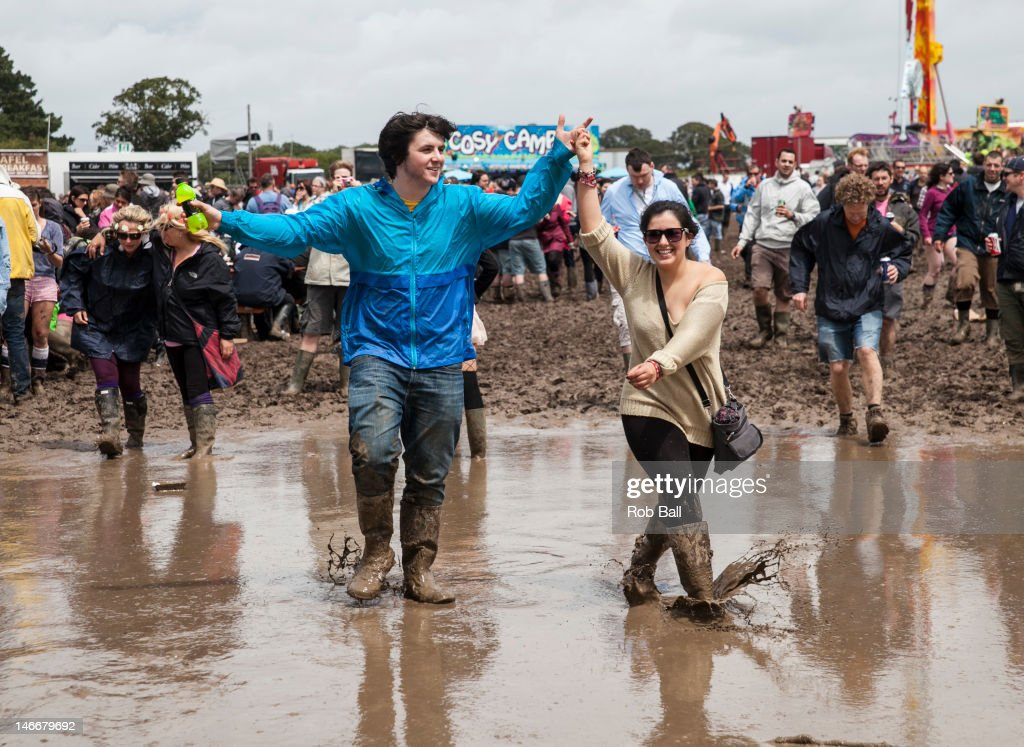 Festival-goers splash around in the mud during the Isle Of Wight Festival 2012 at Seaclose Park on June 22, 2012 in Newport, Isle of Wight.