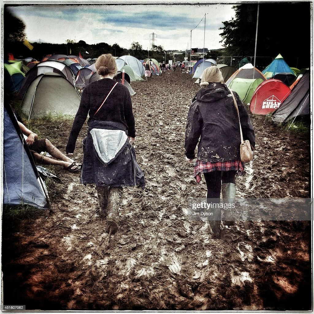 Festival-goers struggle through the mud during the Glastonbury Festival at Worthy Farm in Pilton on June 29, 2014 in Glastonbury, England.