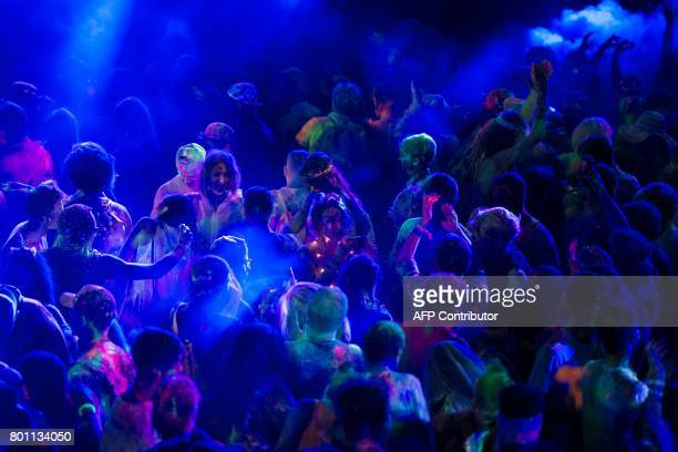 Festivalgoers take part in an ultra violet paint fight in The Common area of the Glastonbury Festival of Music and Performing Arts on Worthy Farm...
