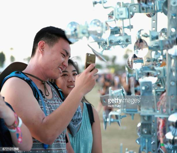 Festivalgoers visit Lamp Beside the Golden Door art installation by Gustavo Prado during day 3 of the 2017 Coachella Valley Music Arts Festival at...
