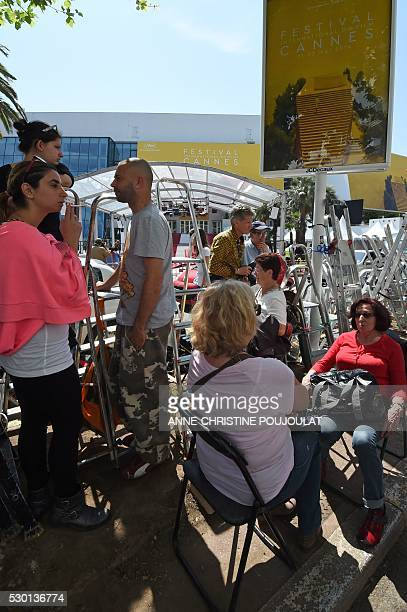 Festivalgoers wait opposite the Festival's Palace in the southeastern French city of Cannes on May 10 2016 on the eve of the opening ceremony of the...