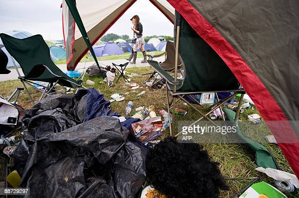 Festival-goers walk past debris in a deserted tent as people begin to pack their bags on the final evening of the annual Glastonbury festival near...
