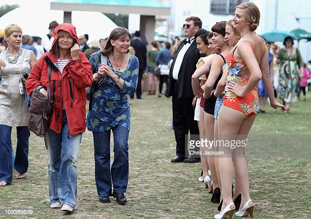 Festivalgoers walk past models in vintage swimwear during Day 1 of the Vintage at Goodwood Festival on August 13 2010 in Chichester England