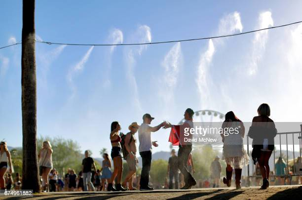 Festivalgoers walk through water misters during day 2 of 2017 Stagecoach California's Country Music Festival at the Empire Polo Club on April 29 2017...