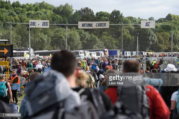 Festival-goers walk towards the exit on the morning after the final night of the Glastonbury Festival at Worthy Farm, Pilton on July 01, 2019 in...