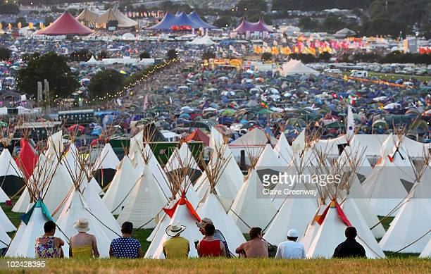 Festivalgoers watch the sun set over the Glastonbury Festival at Worthy Farm Pilton on June 25 2010 in Glastonbury England This year sees the 40th...