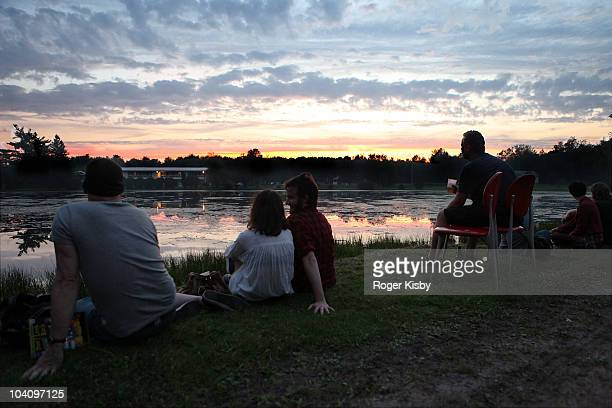Festival-goers watch the sun set over the lake on the first day of All Tomorrow's Parties New York Festival 2010 Day 1 at Kutshers Country Club on...