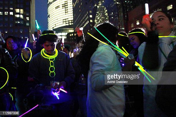 Festivalgoers wave glowsticks at a screening of 'When The Drum Is Beating' during the 2011 Tribeca Film Festival at North Cove at World Financial...