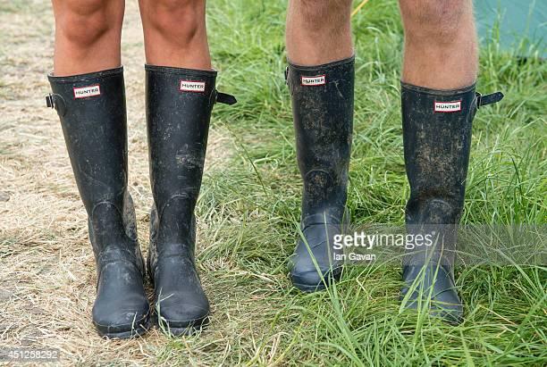 Festivalgoers wear wellington boots in preparation for rain during the Glastonbury Festival at Worthy Farm on June 26 2014 in Glastonbury England