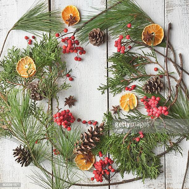 Festive arrangement in wreath shape of pine cones, fruit, berries and pine for Christmas