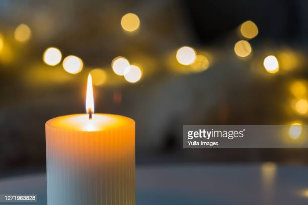 festive background with burning candle and bokeh - candle stock pictures, royalty-free photos & images