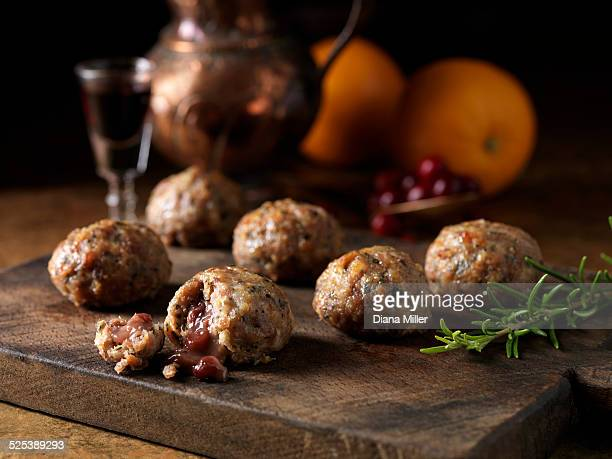 Festive Christmas ingredients of pork, orange, rosemary stuffing balls with port and cranberry sauce centres. Oranges and a glass of red wine