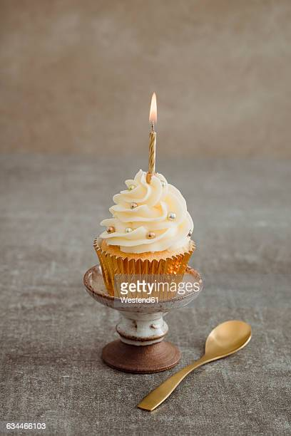 Festive decorated cup cake with lighted candle
