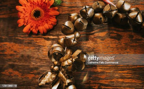 festive flat lay image of jingle bells beside an orange flower on a rustic table - bell stock pictures, royalty-free photos & images