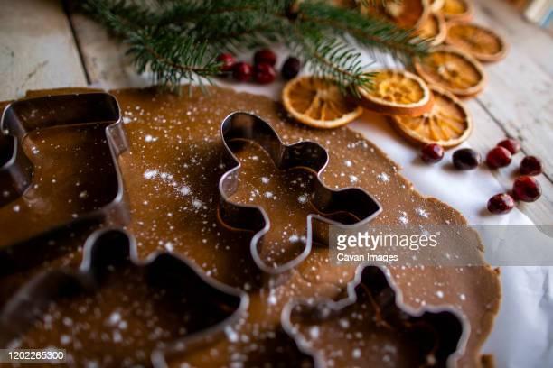 festive gingerbread high side angle shot of cookie cutter on dough - angel hot imagens e fotografias de stock