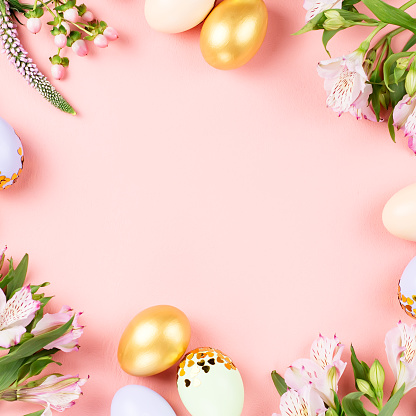 Festive Happy Easter background with decorated eggs, flowers, candy and ribbons in pastel colors on pink. Copy space 1129069217