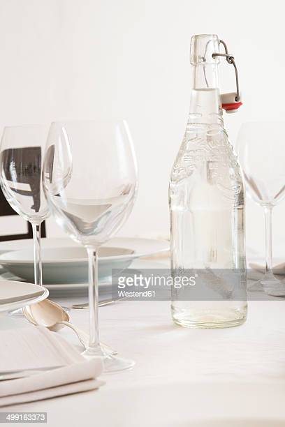 Festive laid table with wine glasses and bottle of water