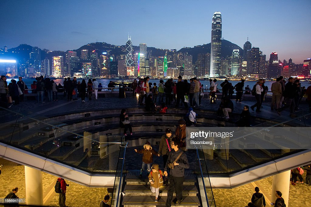 Festive lights illuminate the city skyline as people walk along the waterfront promenade in the Tsim Sha Tsui area of Hong Kong, China, on Saturday, Dec. 22, 2012. Hong Kong's economy is set for its weakest annual expansion since the global financial crisis as the European sovereign debt crisis damps global trade. Photographer: Lam Yik Fei/Bloomberg via Getty Images