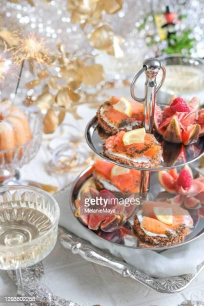 シーフードアペタイザーエタゲレタワーとシャンパンでお祝いのパーティーテーブル - 新年レセプション ストックフォトと画像