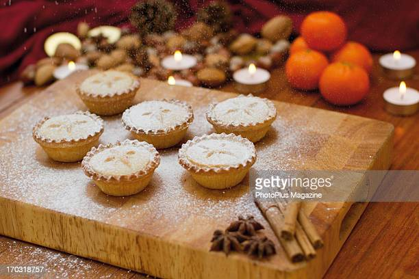Festive scene with mince pies being sprinkled with icing sugar alongside tangerines nuts and cinnamon sticks taken on October 19 2012
