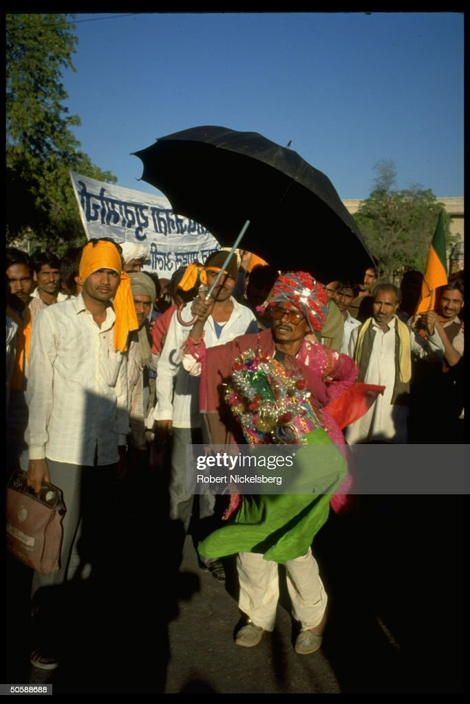 Festive turban clad man holding umbrella : News Photo