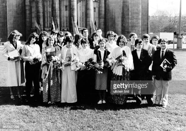 Festlich gekleidete Schüler einer Klasse der 18 Oberschule Hans Janocha in Berlin Prenzlauer Berg stehen mit Blumen und dem Buch Der Sozialismus...