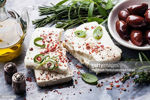 Feta cheese with olives and green herbs on gray marble backgroun