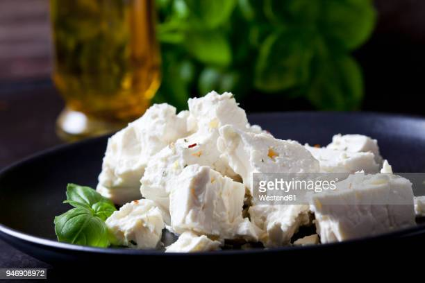 feta, herbes and basil leaves on black plate, close-up - feta cheese stock pictures, royalty-free photos & images
