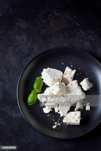 feta, herbes and basil leaves on black plate - feta cheese stock pictures, royalty-free photos & images