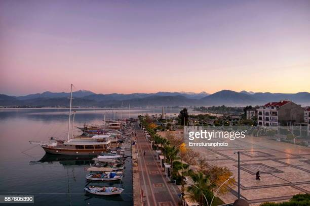 fethiye harbor promenade and park view at dawn with mountains at the background. - emreturanphoto stockfoto's en -beelden