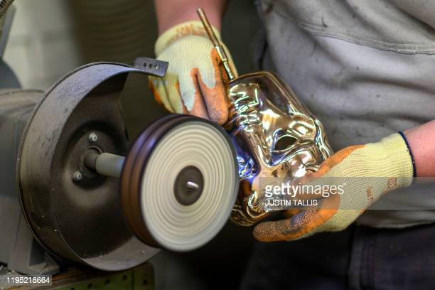 Fettler Piotr Lichon buffs a finished BAFTA mask during a photo call at the New Pro Foundries, west of London, on January 21 ahead of the British...