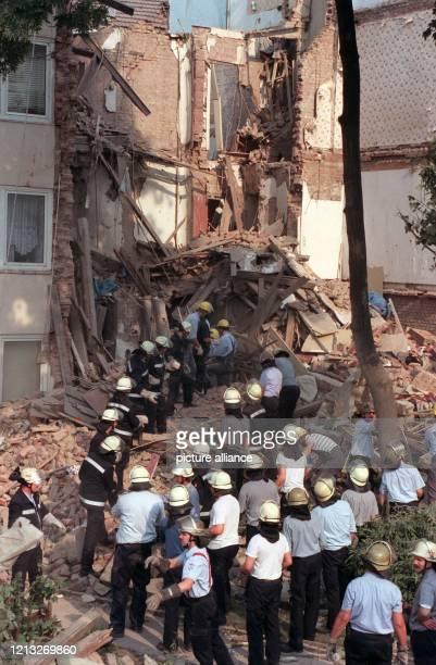 Feuerwehrleute bilden am 24.7.1997 in den Trümmern eines völlig zerstörten Hauses in Düsseldorf eine Kette, um vorsichtig Schutt und Steine...