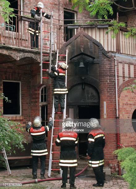 Feuerwehrleute klettern am 30.5.1997 über eine Leiter in das ausgebrannte Behinderten-Wohnheim in Frankfurt/Oder. Bei dem Feuer sind am 29.5. Acht...